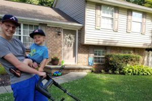 I am holding my son with one hand and a push-mower in the other hand. We are in front of our house.