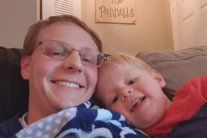 My son and I sitting on the couch together taking smiling