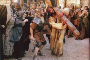 """Picture of Jesus carrying the cross as people scoff at him. Text in image says, """"Are Christians Hospitable to Christ or are we the Romans and Jews scoffing at him?"""