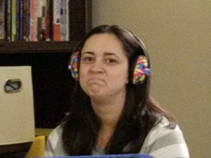 a picture of my wife frowning at me while wearing our sons headphones