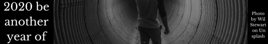 A man looking in fear down a human sized pipe with a flare to light his way.