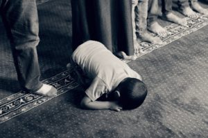 Picture of a child praying, demonstrating the effects of faith and fatherhood