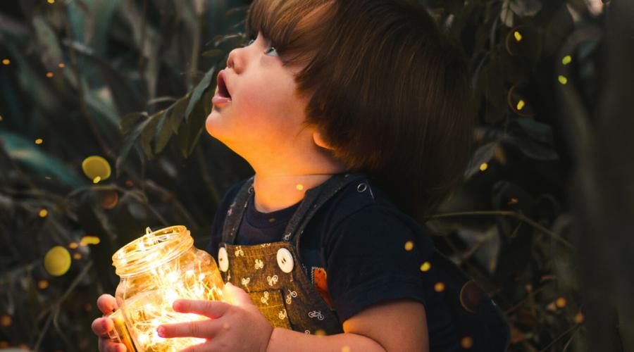 A little boy holding a yellow light in a glass jar.