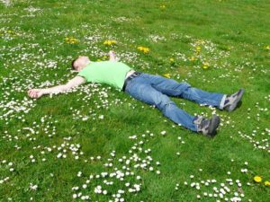 A man lying on grass on a sunny day.