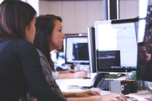 Two women working together on a computer screen