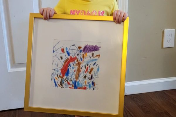 My daughter, Age 2, holding a gift of her artwork in a golden frame.